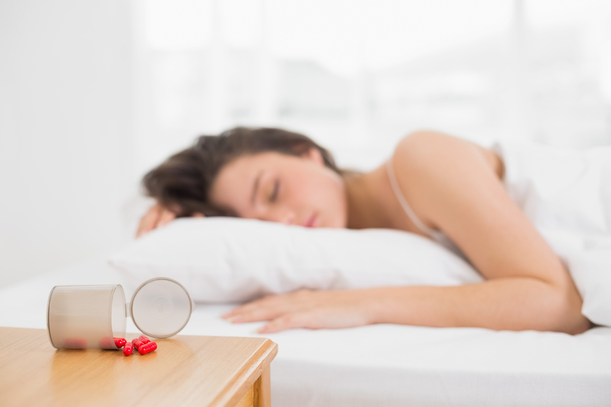 Young woman sleeping in bed by spilt bottle of pills on table at home
